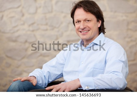 Man relaxing at home in his shirtsleeves sitting in an armchair smiling at the camera - stock photo