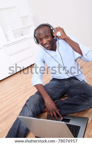 Man relaxing at home with headphones on - stock photo