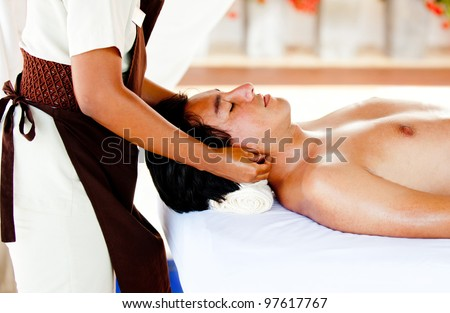 Man relaxing at the spa with a massage on his neck - stock photo