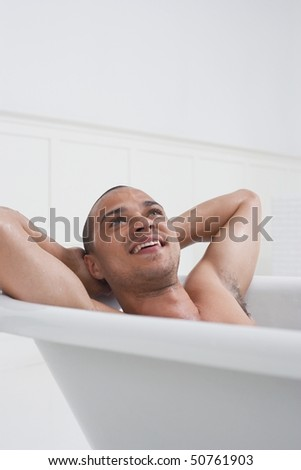 Man relaxing in bathtub - stock photo
