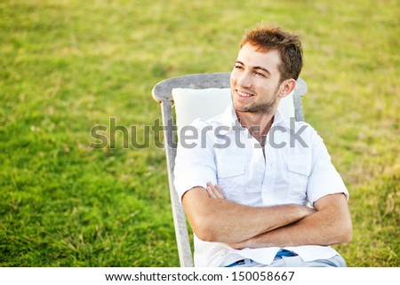 man relaxing in summer on back yard of his house - stock photo