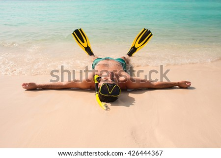 Man, relaxing in the beach, lying on the water with yellow and black flippers fins - stock photo