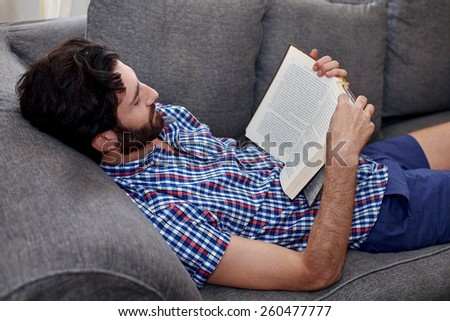 man relaxing on sofa couch reading literature novel story book at home living room lounge - stock photo