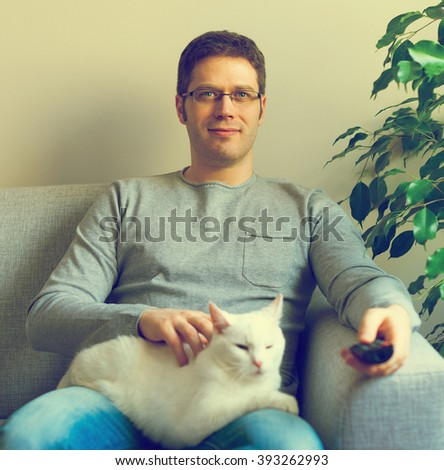Man relaxing on the sofa with tv remote control. Watching TV with his cat. - stock photo