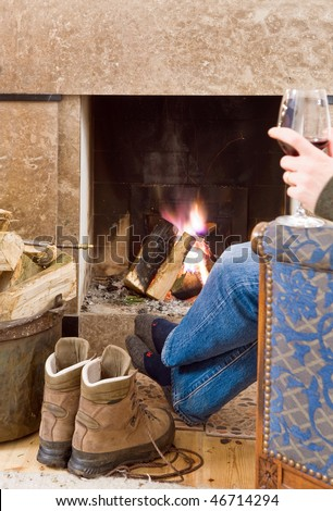 Man relaxing with a glass of red wine by the fireplace after a long hike; his boots off, next to him, warming up - stock photo