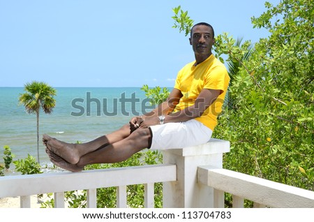 Man relaxing with feet up sitting on a post - stock photo