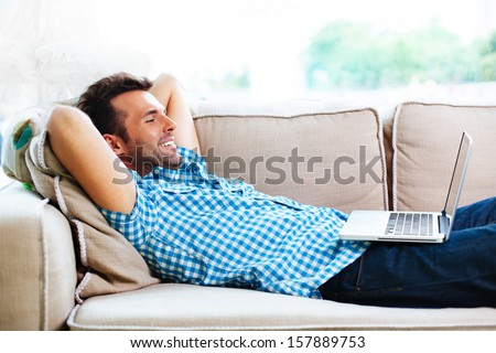Man relaxing with laptop on couch - stock photo