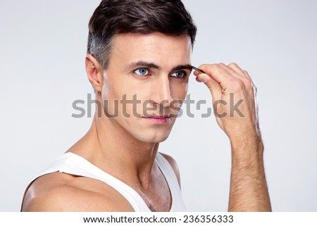 Man removing eyebrow hairs with tweezing - stock photo