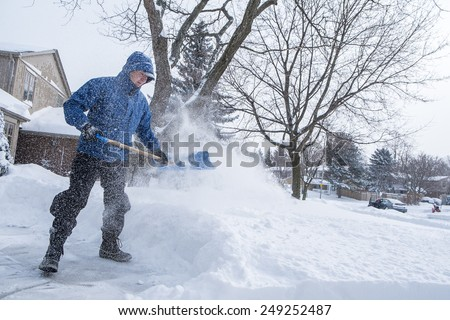 Man Removing Snow with a Shovel  - stock photo