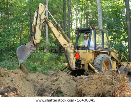 Man removing tree roots with a backhoe - stock photo
