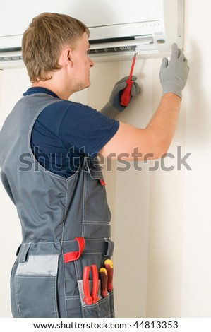 man repair air conditioner - stock photo