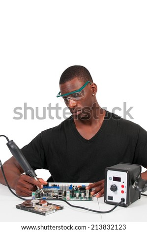 Man repairing a printed circuit board with a forced air soldering iron - stock photo
