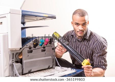 man repairing color printer changing toner cartridge - stock photo