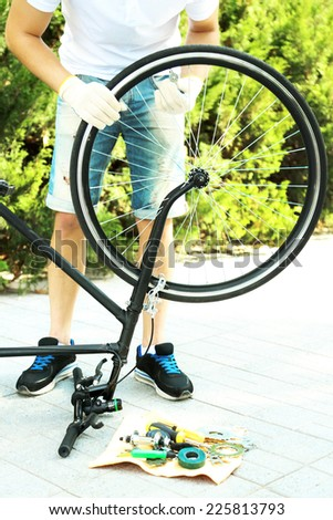 Man repairing his bike, close-up - stock photo