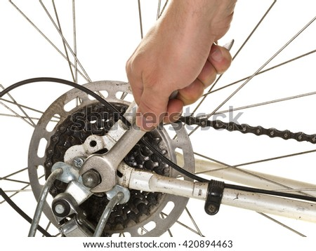 Man repairing rear wheel on a bicycle over white background - stock photo