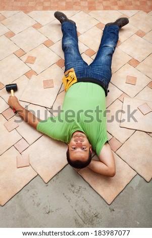 Man resting on ceramic floor tiles he is installing - top view - stock photo