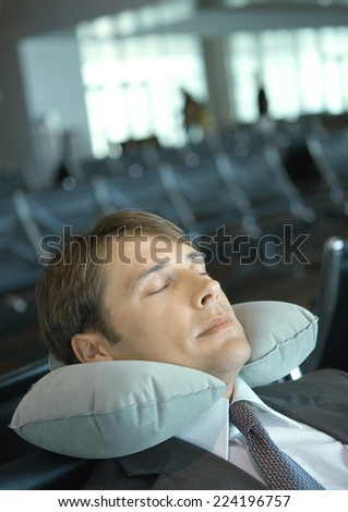 Man resting with neck pillow in airport lounge - stock photo