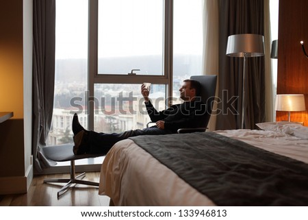 Man resting with whiskey in a hotel room - stock photo