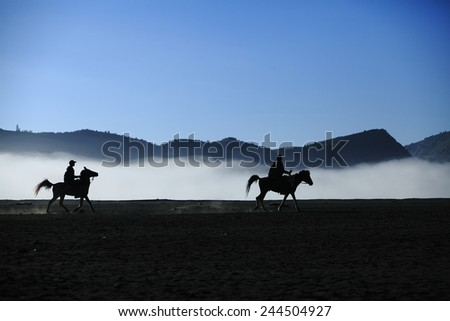 Man ride a horse at Mt. Bromo Indonesia - stock photo