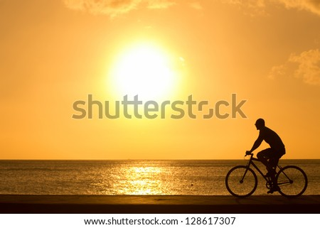 man ride bicycles outdoors against sunset. Silhouette. - stock photo