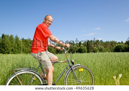 Man riding a bicycle on a field - stock photo