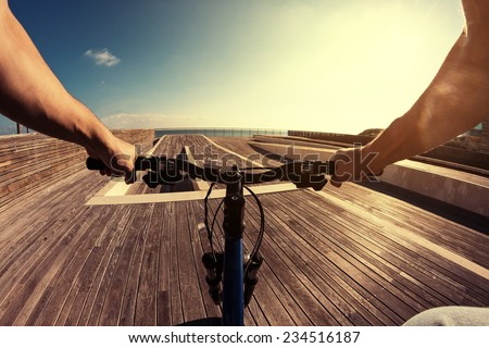 man riding a bicycle on a pier in bright sunlight, POV view - stock photo