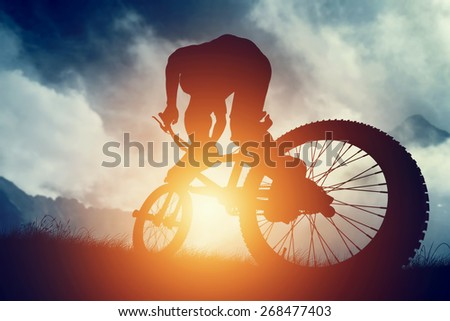 Man riding a bike in high mountains at sunset. Extreme sport, speed, risk. - stock photo