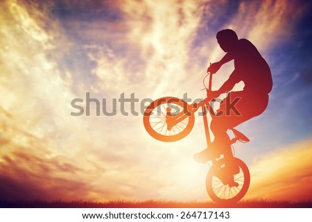 Man riding a bmx bike performing a trick against sunset sky. Extreme sport - stock photo
