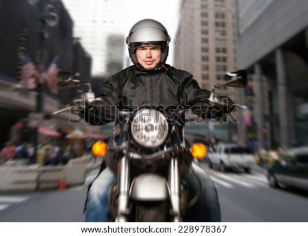 Man riding a motorcycle in a big city - stock photo
