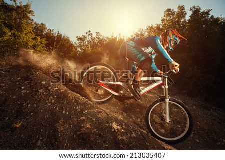 Man riding a mountain bike in downhill style at sunrise. Extreme sports on a bicycle. - stock photo