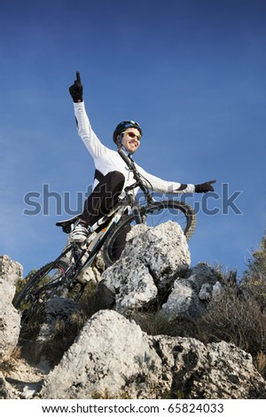 Man riding a mountainbike on mountain rocks - stock photo