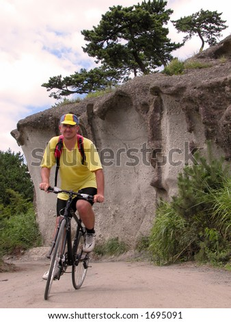 Man riding bicycle in a rocky area. - stock photo