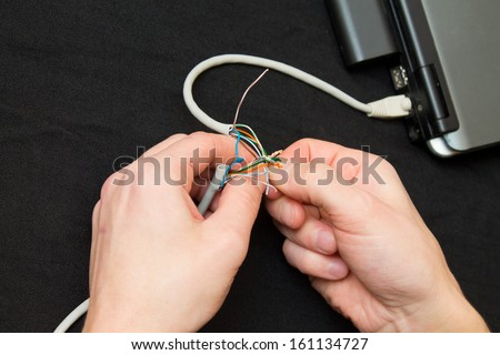 man rolls a network cable - stock photo
