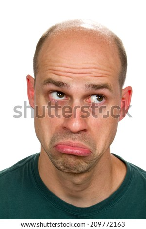 Man rolls his eyes looking upward and thrusts his lips out as he sadly thinks with a humorous expression. - stock photo