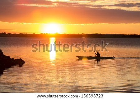 man rowing at sunset in denmark - stock photo