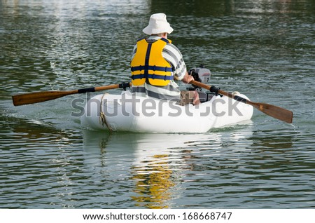 Man rows a rubber inflatable dinghy boat. - stock photo