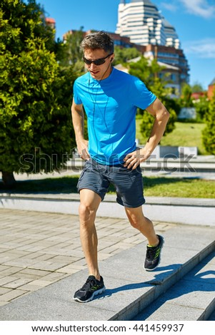 man runner athlete warming up and stretched before jogging along a city bay at the early morning. man training outdoors in park with phone in hand and headphones. man fitness sunset jogging workout - stock photo