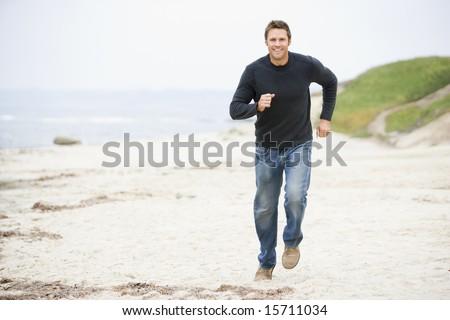 Man running at beach smiling - stock photo