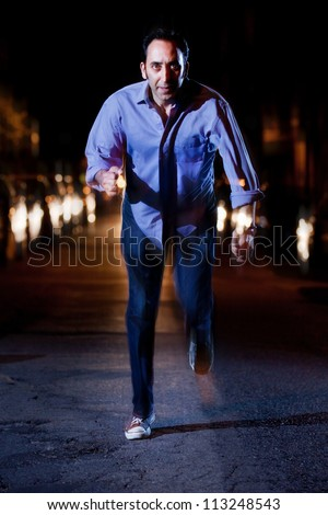 Man running away at night in the middle of a street with car headlights chasing him - stock photo