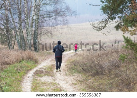 Man running by country rural sandy road at autumnal bad weather. Workout in autumn. - stock photo