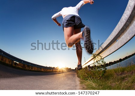 Man running fast on road during sunset. - stock photo