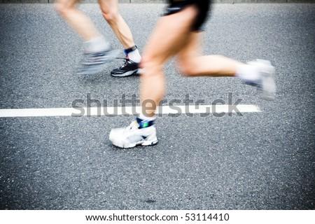 Man running in city marathon, blurred motion - stock photo