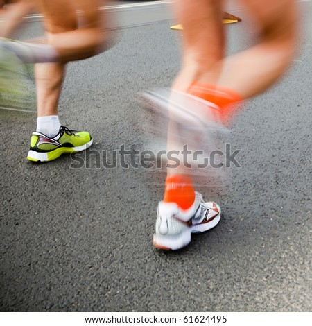 Man running in city marathon - motion blur - stock photo
