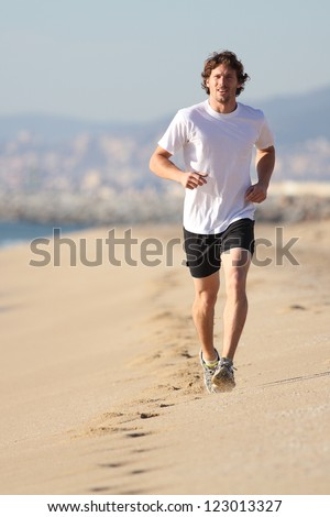 Man running in the beach. Front view - stock photo