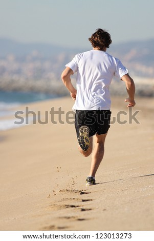 Man running in the beach with his footprints back - stock photo