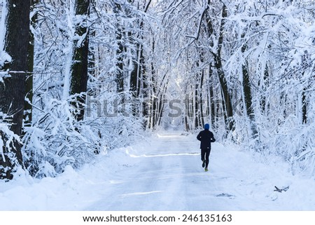 Man running in the forest in winter time - stock photo