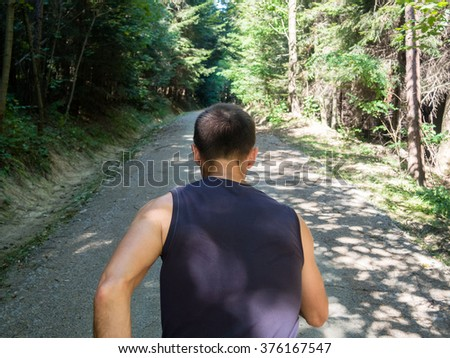 Man running in woods, rear view - stock photo