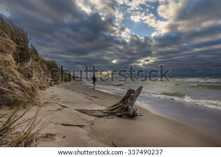 Man running on a Lake Huron beach at sunset as the sun's rays poke thorugh some clouds - Pinery Provincial Park, Ontario, Canada - stock photo