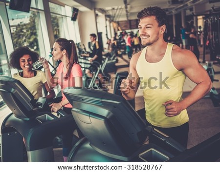 Man running on a treadmill in a gym - stock photo