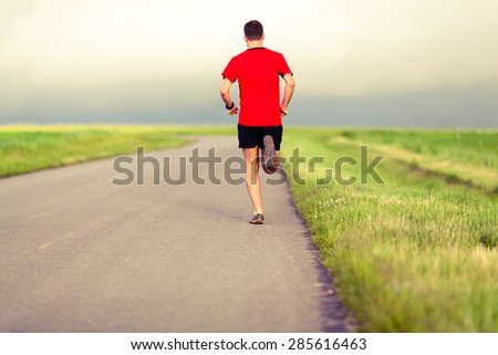 Man running on country road, healthy fitness lifestyle, sport speed training beautiful landscape. Young runner jogging training and doing workout exercising power walking outdoors in nature. - stock photo